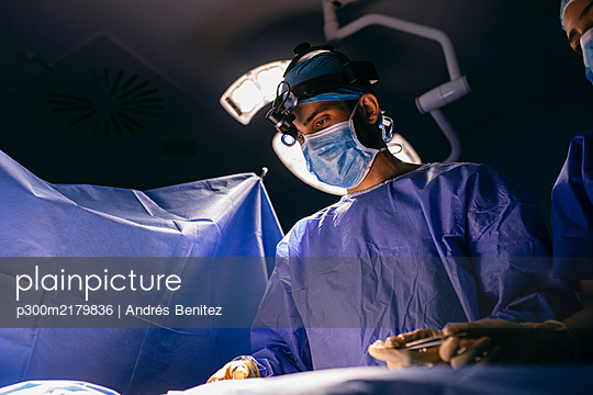 Operating room nurse and surgeon during an operation - p300m2179836 by Andrés Benitez