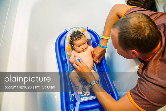 Caucasian father bathing baby boy in bathtub - p555m1421623 by Inti St Clair photography