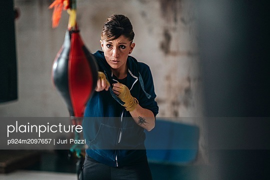 Boxer training with punch bag in gym - p924m2097657 by Juri Pozzi