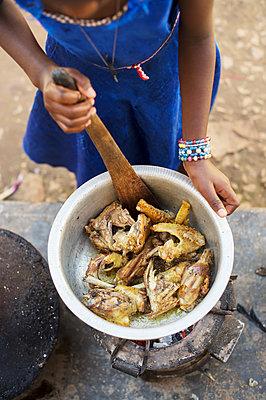 Africa, Uganda, African girl preparing food - p1167m2283463 by Maria Schiffer