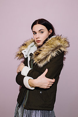 Portrait of a girl in a jacket with a fur collar on pink background - p1363m1332299 by Valery Skurydin