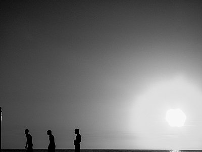 Silhouettes of three persons against the sun - p1484m2150258 by Céline Nieszawer