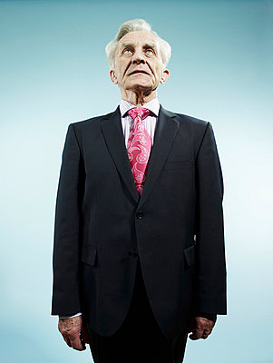 An elegant senior man wearing a suit and pink paisley tie - p30120497f by Carl Smith