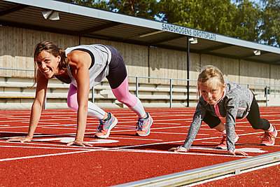 Mother and daughter on running track - p312m1570490 by Lina Arvidsson