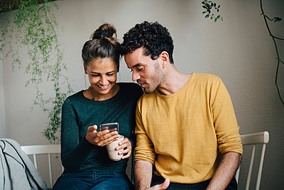Smiling girlfriend showing smart phone to boyfriend while having coffee in living room - p426m2138421 by Maskot