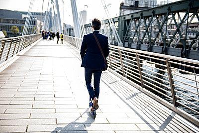 Businessman on scooter, Hungerford Bridge, London, UK - p429m1418035 by Bonfanti Diego