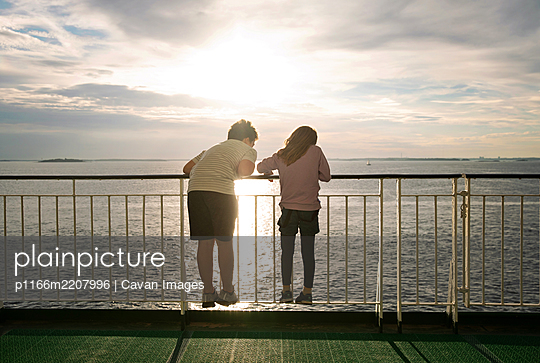 Boy and Girl With Backs to Camera Looking At Ocean From A Ferry - p1166m2207996 by Cavan Images