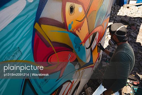 Graffiti artist spray painting on weathered wall  - p1315m2091214 by Wavebreak