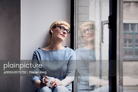 Portrait of smiling woman with coffee mug looking through window - p300m2070732 by Rainer Berg