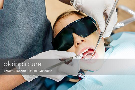 Girl at the dentist receiving treatment - p300m2166589 by Daniel González