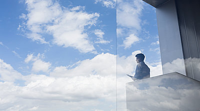 Pensive businessman standing on modern balcony looking at blue sky and clouds - p1023m1519829 by Martin Barraud