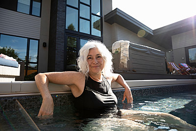 Portrait confident senior woman in sunny, summer swimming pool - p1192m2129521 by Hero Images
