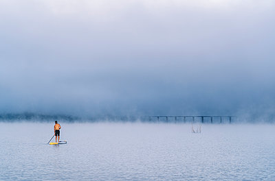 Man stand up paddle surfing on a lake in the fog - p300m2170513 by Daniel González