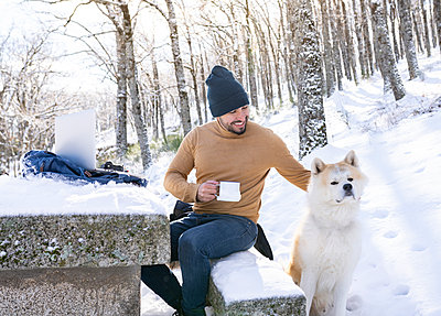 Smiling man holding coffee cup while petting his dog in snowy forest - p300m2242825 by Jose Carlos Ichiro