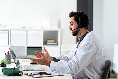 Male doctor wearing headphone while talking on video conference through laptop - p300m2274648 by Giorgio Fochesato