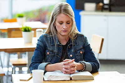 A mature woman praying, after doing some personal Bible study, in a coffee shop; Edmonton, Alberta, Canada - p442m2154444 by LJM Photo