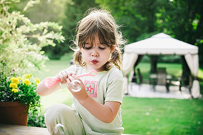 Young Girl Blowing Bubbles Outside In Her Pyjamas On A Summer Morning;Maricourt Quebec Canada - p442m839686 by Patrick La Roque