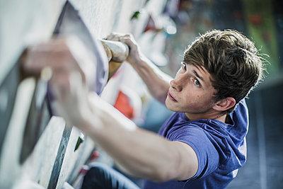 Athlete climbing rock wall in gym - p555m1411962 by John Fedele
