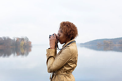 Dark-skinned woman with camera on the lakefront - p975m2228551 by Hayden Verry