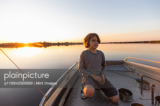 A young boy fishing from a boat on the flat calm waters of the Okavango Delta at sunset - p1100m2300959 by Mint Images