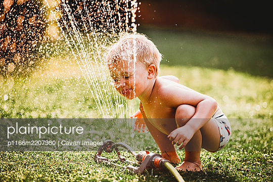 White boy sticking tongue out drinking water from sprinkler in garden - p1166m2207980 by Cavan Images