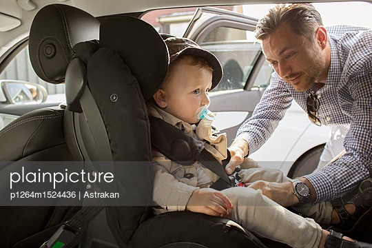 Father fastening son's (18-23 months) seat belt - p1264m1524436 by Astrakan