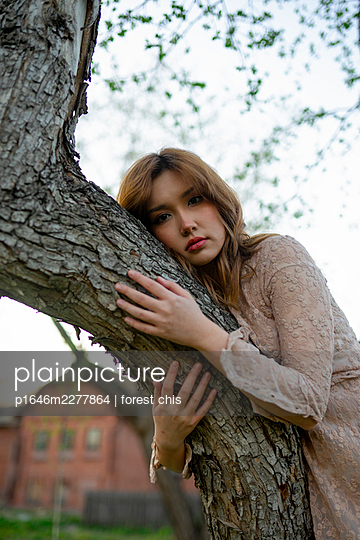 Young woman embracing a tree, portrait - p1646m2277864 by Slava Chistyakov