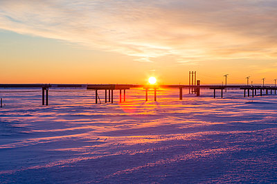 Pipeline on snow covered field against cloudy sky during sunset - p1166m1209357 by Cavan Images