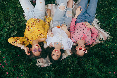 High angle view of happy female friends lying on picnic blanket amidst plants in forest - p1166m2025142 by Cavan Social