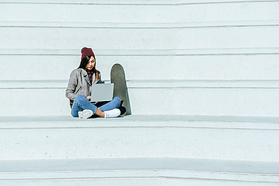 Young woman with skatoboard sitting on stairs outdoors using laptop - p300m2080743 by Kiko Jimenez