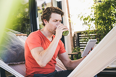 Mid adult man using digital tablet drinking juice while sitting at home - p300m2226697 by Uwe Umstätter
