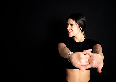 Smiling female athlete looking away while stretching in front of black background - p300m2281932 by Giorgio Fochesato