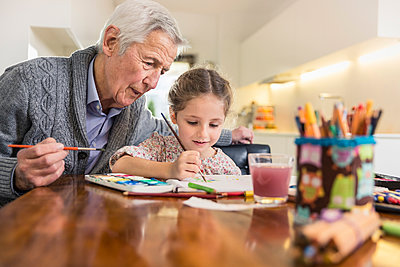 Granddaughter and grandfather painting together at home - p300m2287243 by Stefanie Aumiller