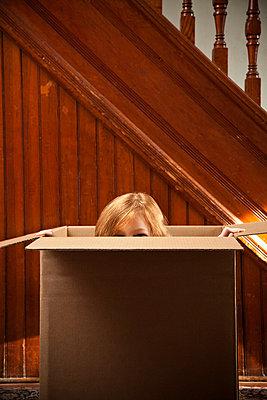 Portrait of girl hiding in cardboard box - p92411079 by Flynn Larsen