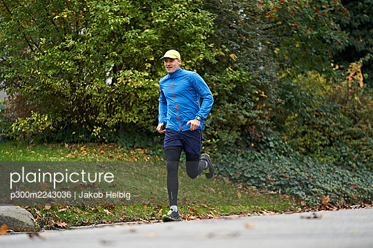 Mature man in sports clothing running on footpath by grass - p300m2243036 by Jakob Helbig