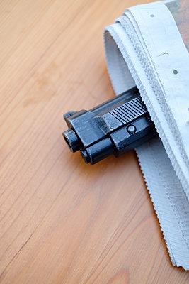 Gun hidden in a newspaper - p1228m1553073 by Benjamin Harte