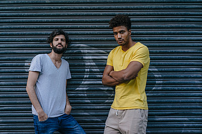 Two friends standing at roller shutter in the city - p300m1535762 by Kniel Synnatzschke