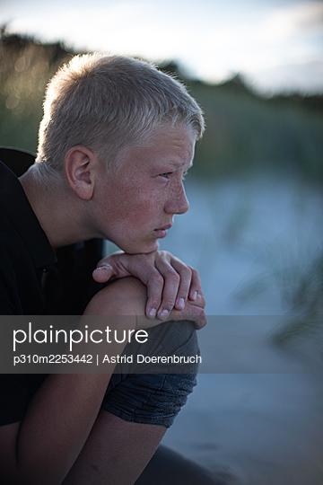 Junge sitzt am Strand - p310m2253442 von Astrid Doerenbruch