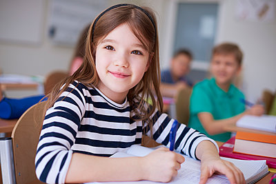 Portrait of smiling schoolgirl writing in exercise book in class - p300m1587765 by gpointstudio