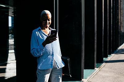 Smiling businesswoman with folder using phone in city - p300m2206768 by Josep Rovirosa
