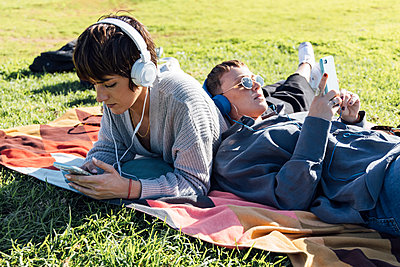 two women chilling and listening music on headphone in the riverside, Seville, Spain - p300m2252421 von Julio Rodriguez