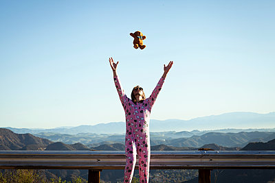 Man wearing pink onesie throwing teddy bear in mid air, Malibu Canyon, California, USA - p924m1422752 by Raphye Alexius