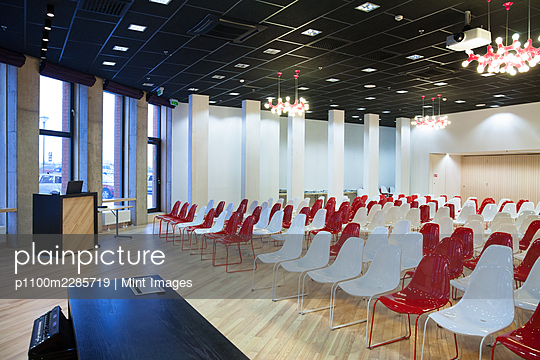 Large empty room with red and white chairs in rows - p1100m2285719 by Mint Images