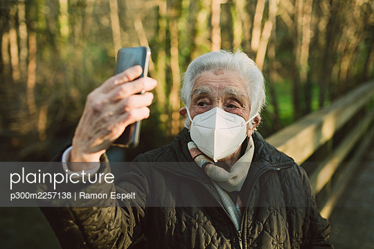 Senior woman wearing protective face mask while taking selfie through smart phone in winter - p300m2257138 by Ramon Espelt