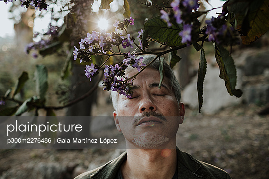 Mature man with eyes closed below blossoming tree in garden - p300m2276486 by Gala Martínez López