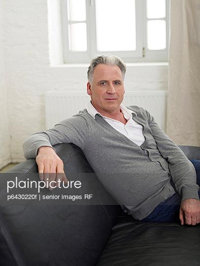 Aelterer Mann sitzt auf dem Sofa  - p6430220f von senior images RF