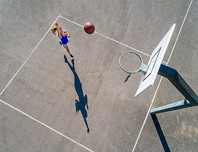 Aerial view of young woman playing basketball - p300m2114936 by Stefan Schurr