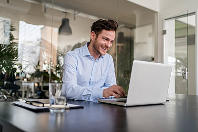 Smiling businessman using laptop at desk in office - p300m2265208 by Daniel Ingold