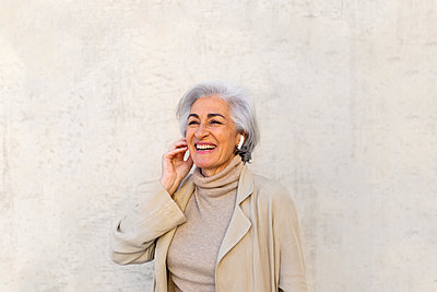 Happy woman listening music through wireless headphones in front of wall - p300m2281474 by PICUA ESTUDIO