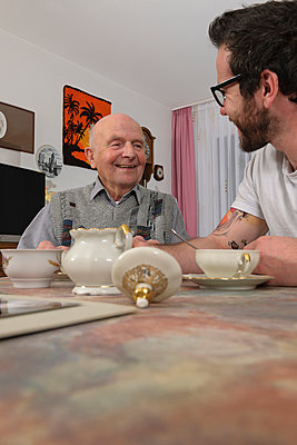 Grandfather and grandson drinking coffee at home - p300m911320f by Albrecht Weißer